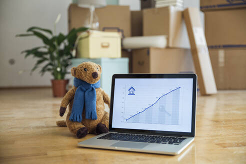 Teddy bear and rising line graph on laptop screen in front of cardboard boxes in a new home - MAMF00852