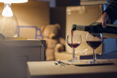 Hand pouring wineinto glasses on cardboard box in a new home - MAMF00864