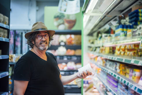 Portrait of senior man buying food in a supermarket - CJMF00116