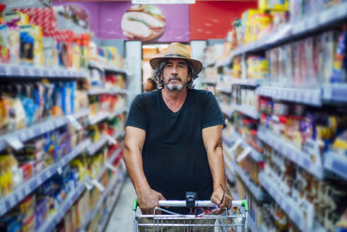 Portrait of a senior man shopping in a supermarket - CJMF00119