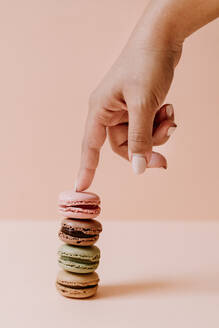 female hand touching macarons on pink background - JMHMF00002