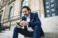 Portrait of bearded mature businessman sitting on stairs looking at cell phone - JLOF00323