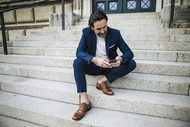 Bearded mature businessman wearing blue suit sitting on stairs looking at cell phone - JLOF00338