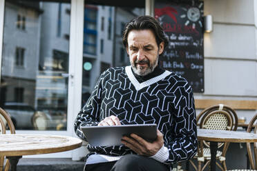 Portrait of fashionable mature man using digital tablet at pavement cafe - JLOF00344