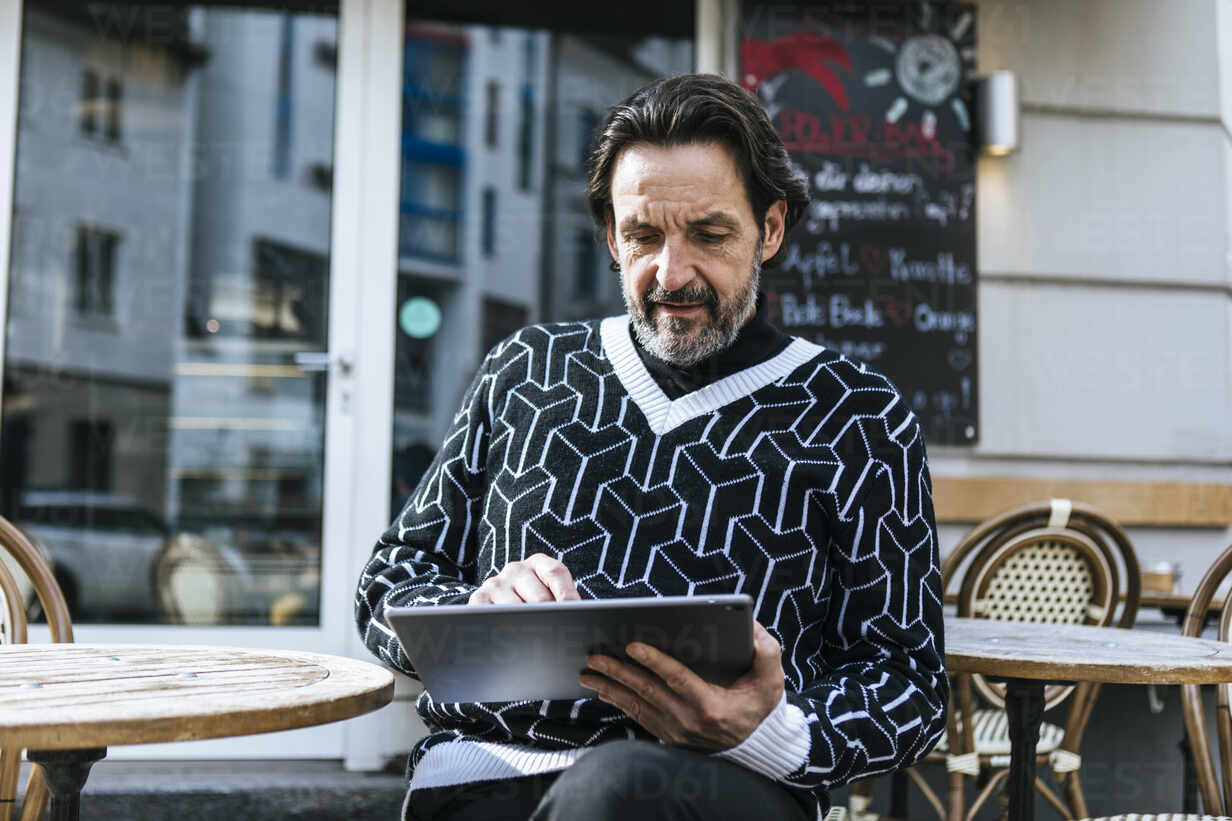 Portrait of fashionable mature man using digital tablet at pavement cafe - JLOF00344 - Johanna Lohr/Westend61