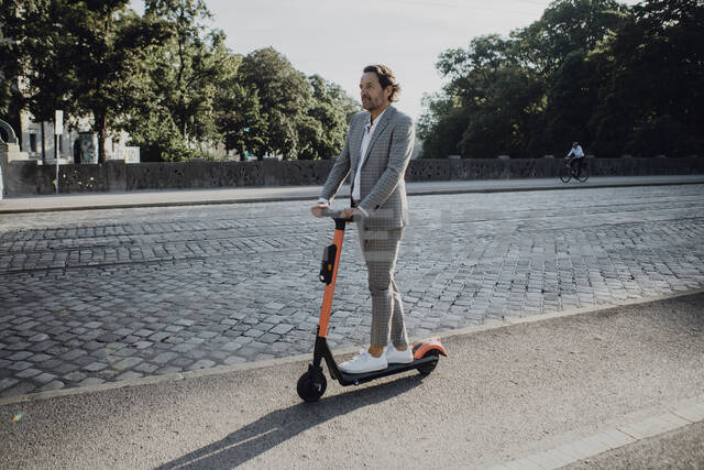 Businessman with e-scooter in the city - JLOF00368 - Johanna Lohr/Westend61