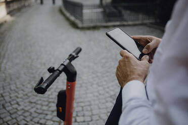 Businessman renting an e-scooter using smartphone - JLOF00380