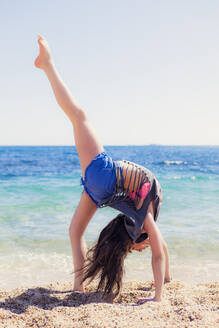 Girl doing gymnastics on the beach - XCF00281