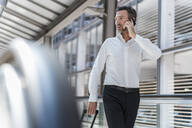 Businessman on escalator talking on the phone - DIGF08461