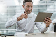 Businessman using tablet in a cafe - DIGF08467