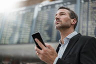 Portrait of businessman with cell phone at arrival departure board at the airport - DIGF08476