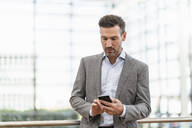 Portrait of businessman using cell phone - DIGF08482