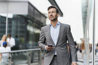 Portrait of businessman with cell phone on the go - DIGF08491