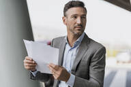 Portrait of businessman holding papers outdoors - DIGF08500