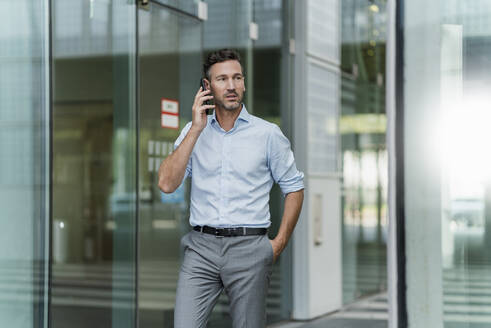 Businessman on the phone outside building - DIGF08506
