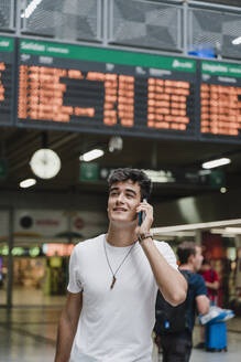 Young man waiting at train station and using smartphone - JMHMF00021