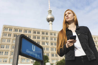 Portrait of redheaded young woman with smartphone at Alexanderplatz, Berlin, Germany - WPEF01997