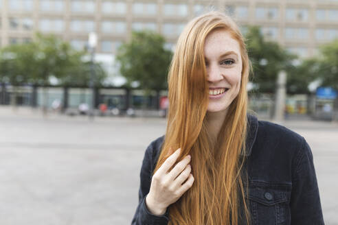 Portrait of redheaded young woman at Alexanderplatz, Berlin, Germany - WPEF02003