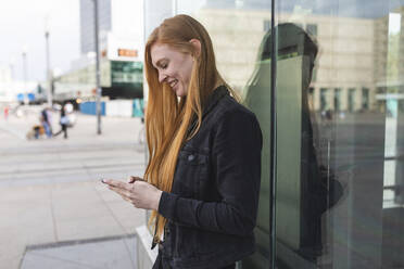 Redheaded young woman text messaging, Berlin, Germany - WPEF02006