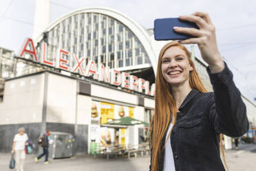 Portrait of redheaded young woman  taking selfie with smartphone at Alexanderplatz, Berlin, Germany - WPEF02009