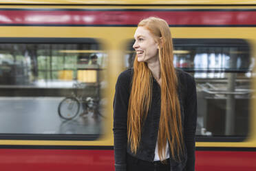 Laughing redheaded young woman waiting at platform, Berlin, Germany - WPEF02012