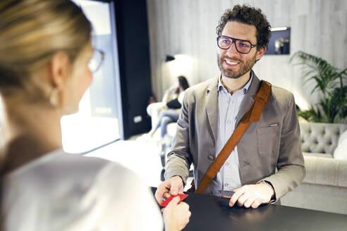 Smiling businessman handing over credit card at reception - JSRF00662