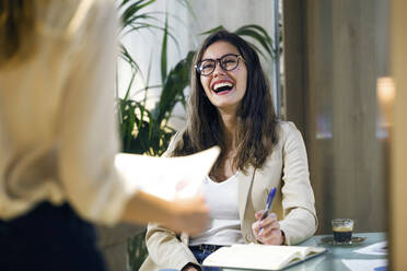 Laughing businesswoman looking at colleague in modern office - JSRF00686