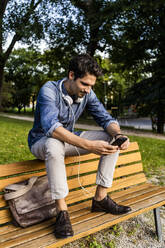 Smiling man sitting on a park bench using his smartphone - GIOF07172