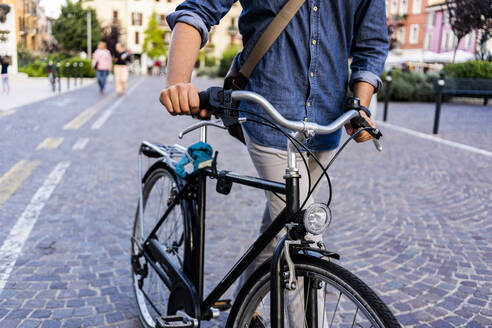 Man pushing a bicycle in the city - GIOF07175