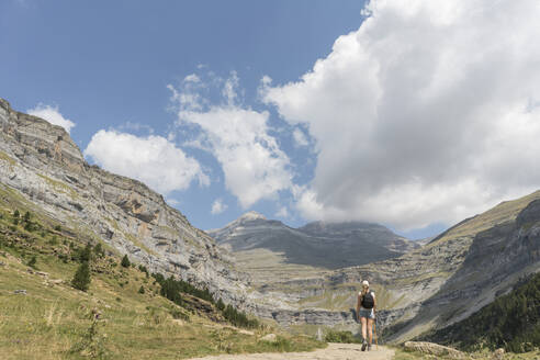 Rear view of woman walking on a trail in mountains, Ordesa national park, Aragon, Spain - AHSF00856