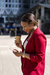 Smiling businesswoman with coffee to go looking at mobile phone, London, UK - MAUF02941