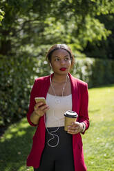 Portrait of businesswoman with coffee to go listening music with smartphone and earbuds, London, UK - MAUF02944