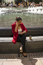 Businesswoman on the phone checking the time, London, UK - MAUF02947