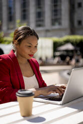 Portrait of smiling businesswoman working on laptop outdoors, London, UK - MAUF02953