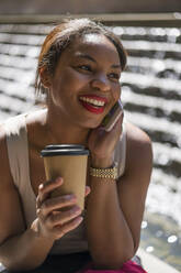 Portrait of happy woman with coffee to go on the phone, London, UK - MAUF02959