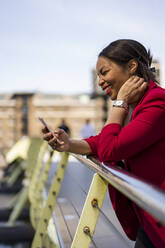 Portrait of smiling businesswoman leaning on bridge railing looking at cell phone, London, UK - MAUF02962
