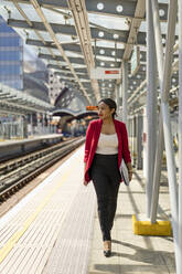 Businesswoman walking on platform, London, UK - MAUF02968