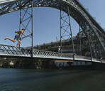 Young man jumping from bridge into the water, Porto, Portugal - AHSF00861