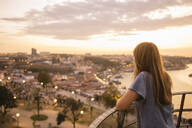 Woman watching panoramic view of Porto at sunset, Portugal - AHSF00864