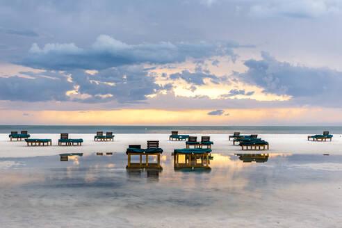 USA, Florida, Cloudy sky over deck chairs on empty coastal beach ofGulf of Mexicoat dusk - EGBF00359