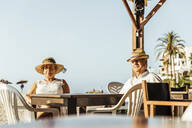 Senior couple sitting at a bar terrace at the beach, El Roc de Sant Gaieta, Spain - MOSF00026
