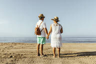 Rear view of senior couple on the beach, El Roc de Sant Gaieta, Spain - MOSF00029