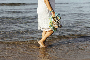 Close-up of senior woman wading in the sea, El Roc de Sant Gaieta, Spain - MOSF00032