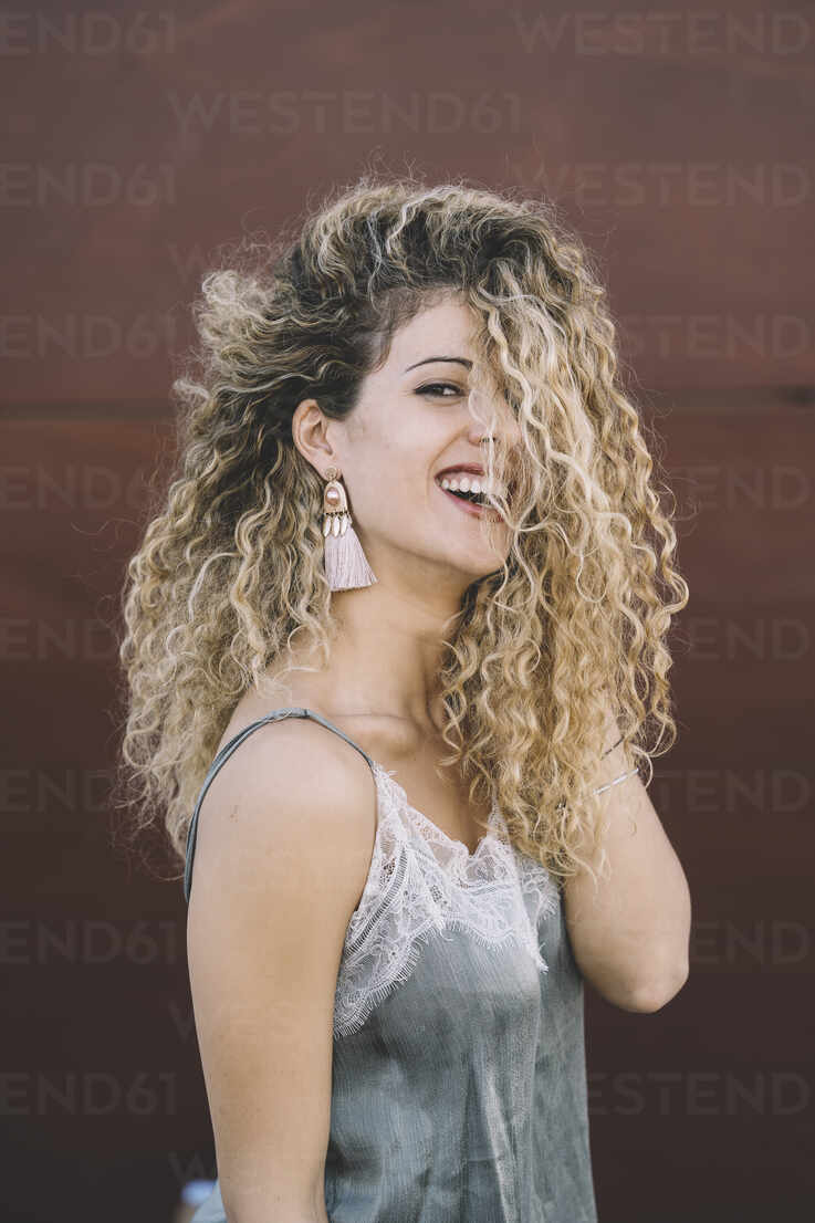 Portrait of laughing young woman with dyed blond ringlets - DAMF00138 - David Agüero Muñoz/Westend61