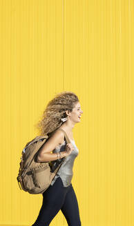Young woman carrying backpack in front of yellow background - DAMF00141