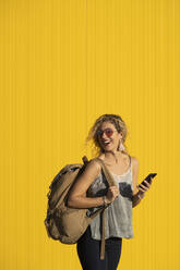 Laughing young woman with  backpack and cell phone standing in front of yellow background - DAMF00144