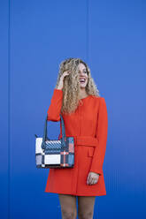 Portrait of young woman with stylish bag wearing red dress in front of blue background - DAMF00147