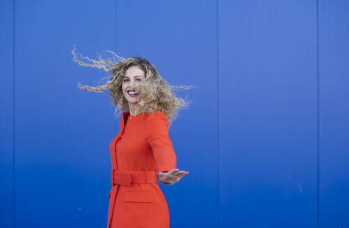 Portrait of happy young woman wearing red dress in front of blue background - DAMF00150