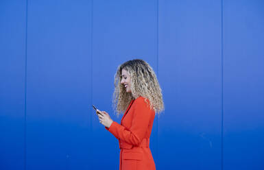 Profile of young woman wearing red dress in front of blue background looking at cell phone - DAMF00153