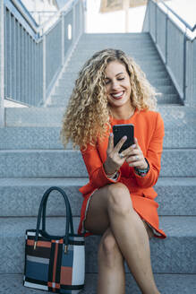 Portrait of happy young woman wearing red dress sitting on stairs using smartphone - DAMF00159